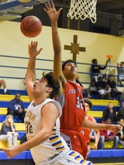 John Carroll Catholic's Raul Guevara (left) shoots with St. Lucie West Centennial's Najee Leon defends Wednesday, Jan. 17, 2018, during their high school boys basketball game at John Carroll Catholic High School in Fort Pierce. To see more photos, go to TCPalm.com.