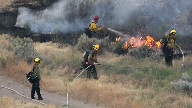 In this June 30, 2016, photo, firefighters respond to a wildfire near the Morningside Heights neighborhood near Table Rock in east Boise, Idaho.   A new study on Western forest fires confirms what is already apparent — wildfire seasons are getting longer and more destructive. But researchers with the University of Idaho and Columbia University also say humans are to blame for much of that increase.