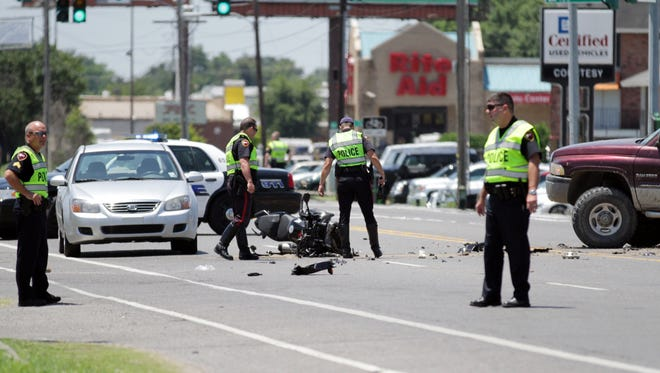 Lafayette Police work a crash involving a motorcycle crash around noon Wednesday, July 30, 2014, in the 5500 block of Johnston Street in Lafayette, La.