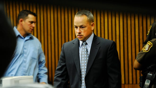 Detroit Police Officer Joseph Weekley comes back into the courtroom during the first day of testimony at the Frank Murphy Hall of Justice in Detroit, Michigan on Thursday, Sept. 18, 2014.