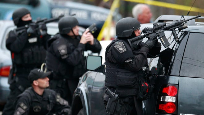 Police in tactical gear surround an apartment building while looking for a suspect in the Boston Marathon bombings in Watertown, Mass., April 19, 2013. The bombings on April 15 killed three people and injured more than 250.