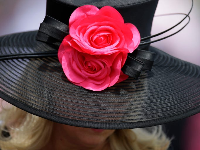 A woman looks over a racing program before the 140th running of the Kentucky Derby horse race at Churchill Downs Saturday, May 3, 2014, in Louisville, Ky.