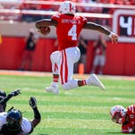 Nebraska quarterback Tommy Armstrong Jr. (4) leaps over Southern Miss linebacker D'Nerius Antoine (12) during a game earlier this season.