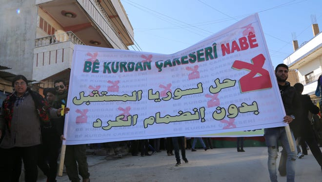 """Kurdish demonstrators hold a banner reading in Arabic: """"No solution for Syria's future without the inclusion of the Kurds"""" during a demonstration against the exclusion of Syrian-Kurds from the Geneva talks in the northeastern Syrian city of Qamishli on Feb. 4, 2016."""