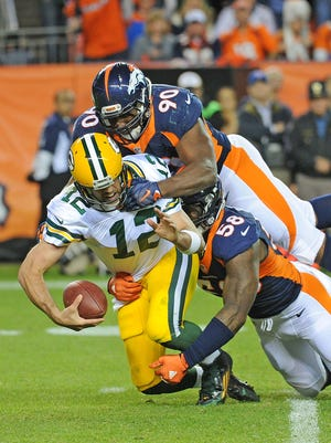 Green Bay Packers quarterback Aaron Rodgers (12) is sacked in the fourth quarter by Denver Broncos defensive end Antonio Smith (90) and outside linebacker Von Miller (58) against the Denver Broncos at Sports Authority Field November 1, 2015.