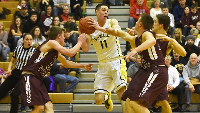 Tri-Valley's Jake McLoughlin pulls down a contested rebound against John Glenn Friday night in Dresden.