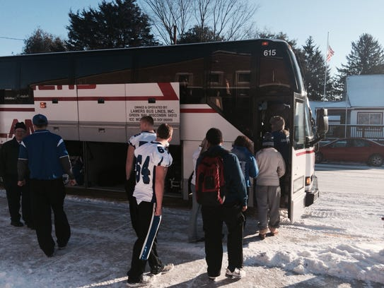 Amherst High School football players board the bus
