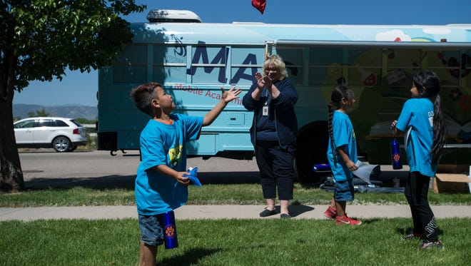Tavelli Elementary School second grader Teddy Ortega, 6, practices juggling while principal Christine Hendricks cheers him on in front of Poudre School District's Mobile Academic Classroom on Monday, June 11, 2018, at the Bull Run Apartment complex in Fort Collins, Colo.