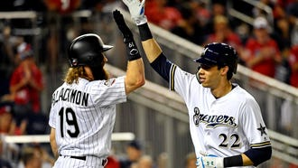 Christian Yelich of the Milwaukee Brewers (22) celebrates National League outfielder Charlie Blackmon of the Colorado Rockies (19) after hitting a home run during the eighth inning against the American League in the 2018 MLB All Star Game at Nationals Ballpark.