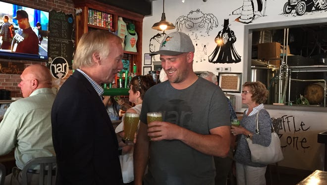 Maryland Comptroller Peter Franchot, left, clinks glasses with RaR Brewing's J.T. Merryweather at the brewery's Cambridge, Maryland location on Tuesday, June 27.
