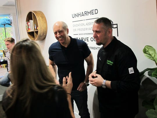 Delicious Raw owner Flemmong Madsen, center, and Chef Scott Boyd, right, chat with a patron April 20, 2017, during an event at the location in Pine Ridge Crossing in North Naples.