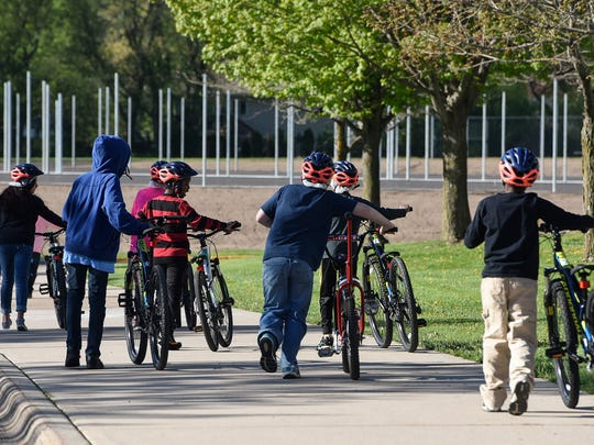 Fourth-grade students take their bikes at the start of physical education class Thursday, May 11, at Discovery Community School in Waite Park.