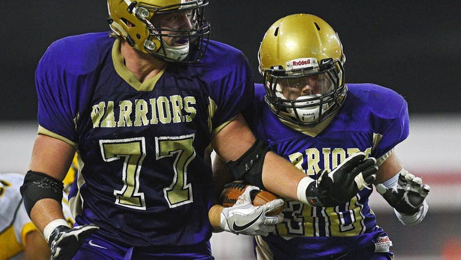Winner's Ty Bolton (30) carries the ball in for a touchdown as teammate John Kludt (77) blocks during the 2016 South Dakota State Class 11B Football Championship game against Groton Area Friday, Nov. 11, 2016, at the DakotaDome on the University of South Dakota campus in Vermillion, S.D.