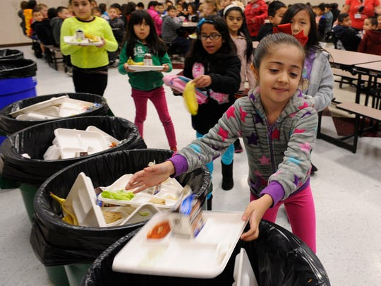 Children at Manuel Hernandez Elementary School separate their lunch waste into trash, composting and recycling containers in their cafeteria after eating lunch. Here we see them putting compostable trays, food waste and milk cartons into the compost bins.