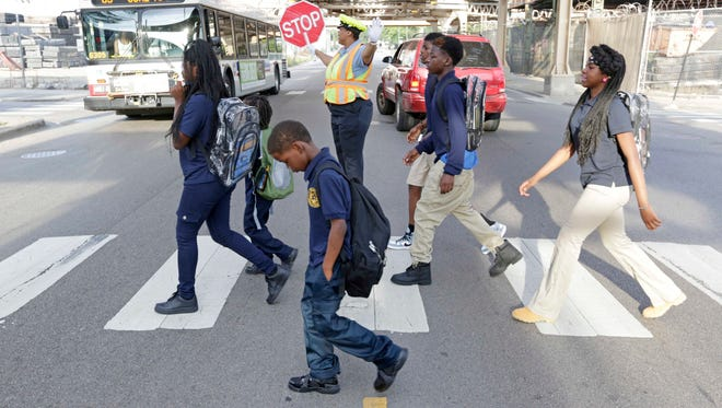 Schoolchildren walk a safe passage route along 63rd Street as crossing guard Patricia Howard stops traffic on Sept. 2, 2014, in Chicago.
