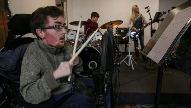 Zach Mecham, a Drake University student and advocate for people with disabilities, plays drums on Wednesday, Dec. 16, 2015, during a Worship Workshop rehearsal at the Pleasantville Church of Christ. Mecham is a drummer for the group, which provides music for services at the church.