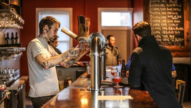 General Manager/Bartender, Chris Porter, left, and Bartender Craig Gorsline, left/ behind, serve up brews at Central State Brewery's  Koelschip Tap Room's soft opening.