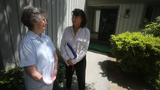 Leslie Fulton, secretary of one of the homeowners associations at Heritage Hills in Somers, left, speaks with Karen Jahn, property manager with Heritage Management Services, in front of one of the several abandoned condominium units at Heritage Hills. The unit has been abandoned for about three years.