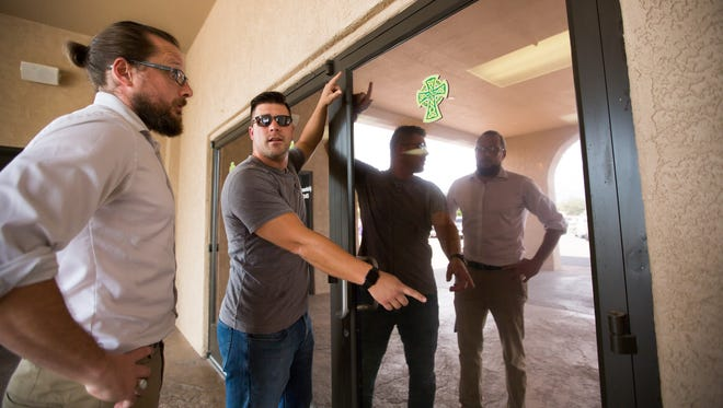 Holy Cross Pastoral Associate of Administration Wade Cornelius, right, points out Monday, Aug. 1, 2016, a spot where glass was damaged to lay minister Craig Bullock. On Aug. 2, 2015 an explosive in a trash can outside of Holy Cross Church damaged the building's doors and walls.