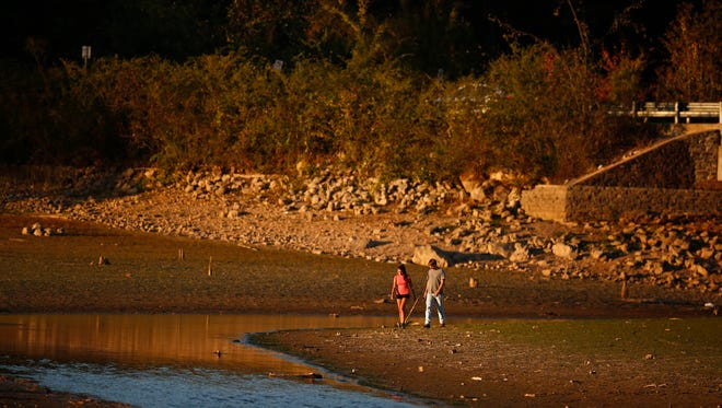 A couple walks near Lake Purdy, where water levels have dropped several feet due to a severe drought, Tuesday, Oct. 11, 2016, in Birmingham, Ala. La Nina could mean ongoing drought conditions across the nation's southern tier.