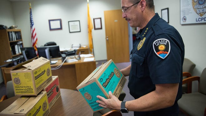 "Las Cruces Police Chief Jamie Montoya, after digging through a few boxes of cookies, carries a box of ""Thanks-A-Lot"" Girl Scout cookies in to his office Thursday July 20, 2017. The Red Cross delivered 38 cases of Girl Scout cookies to the Las Cruces Police Department to say thank you for their service."