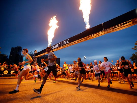 The first group of marathon runners take off from the starting line at 6:30 am during the 20th Annual Flying Pig Marathon in downtown Cincinnati on Sunday, May 6, 2018.