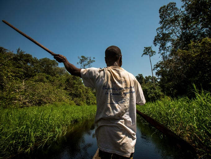 Mossimbo Eric paddles a pirogue, which is a long narrow