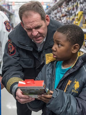 Livonia Fire Chief Shadd Whitehead helps Isaiah Taylor with a handheld video game.