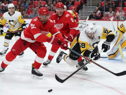 Pittsburgh Penguins defenseman Kris Letang (58) passes the puck away from Detroit Red Wings center Frans Nielsen (51) during the second period of an NHL hockey game Tuesday, March 27, 2018, in Detroit. (AP Photo/Carlos Osorio)