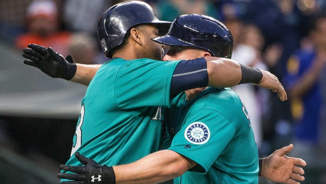 Seattle Mariners' Nelson Cruz, left, welcomes home Kyle Seager after Seager's home run in the sixth inning of a baseball game against the Baltimore Orioles on Friday, July 1, 2016, in Seattle. (Dean Rutz/The Seattle Times via AP)