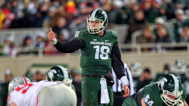 Nov 8, 2014; East Lansing, MI, USA; Michigan State Spartans quarterback Connor Cook (18) gestures to sidelines  during the 2nd half of a game against Ohio State at Spartan Stadium.