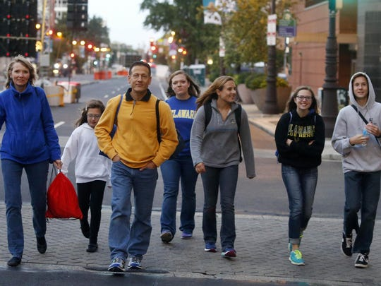 Joan and Joe Fassano of Pike Creek walk up Broad Street in Philadelphia with family friend Amanda Clarke (fifth from left) and their children, from left, Bryna, Maggie, Bridget, Joseph on their way to the papal Mass on the Benjamin Franklin Parkway on Sunday.