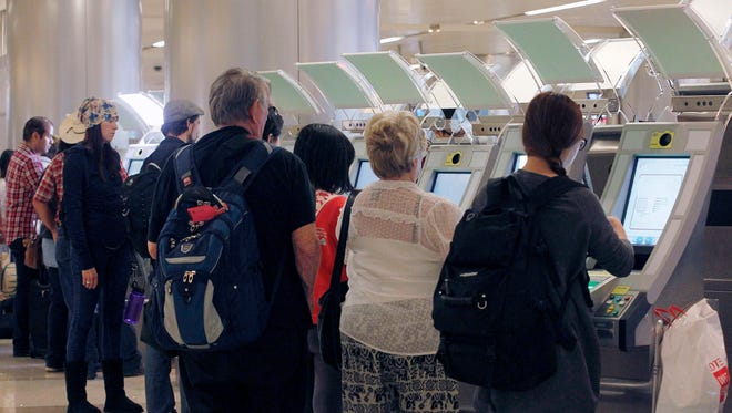 Passengers arriving from abroad use automated passport kiosks as they get ready to go through Customs.