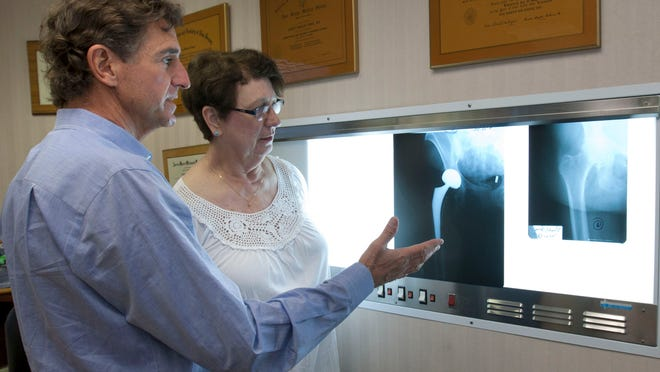 A doctor and patient look at before (right) and after X-rays of her hip after he performed hip replacement surgery on her.