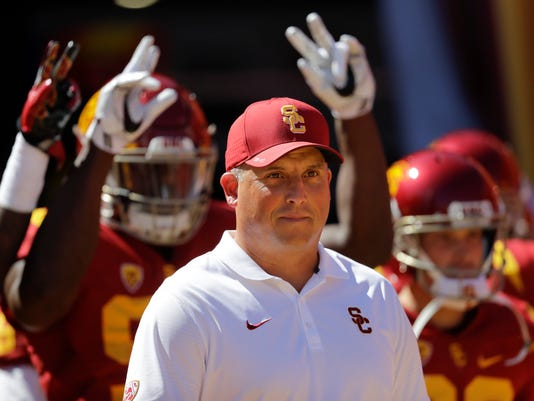 FILE - In this Oct. 8, 2016, file photo, Southern California coach Clay Helton leads his players onto the field before an NCAA college football game against Colorado in Los Angeles. USC plays Western Michigan, Texas, and Notre Dame in nonconference games this season. (AP Photo/Jae C. Hong, File)