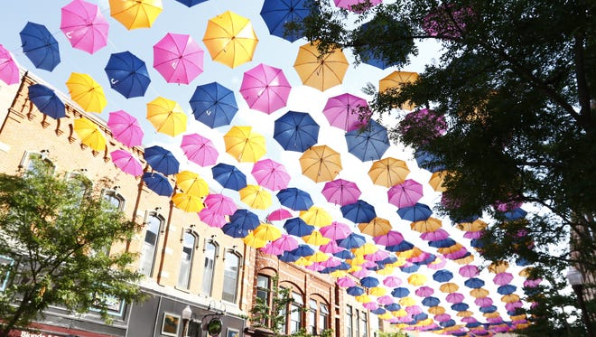 Pedestrians enjoy the sight of hundreds of colorful umbrellas suspended over Third Street in downtown Wausau.