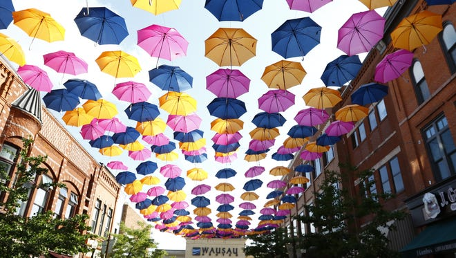 Pedestrians enjoy the sight of hundreds of colorful umbrellas suspended over Third Street in downtown Wausau, just in front of the Wausau Center mall.