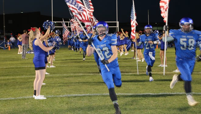 Snowflake football players lead their team onto the field during a game.