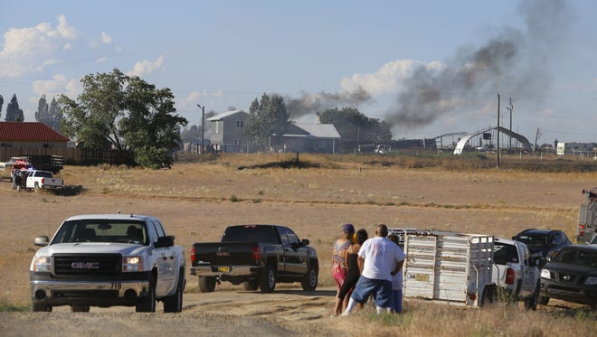 Members of the Tsosie family watch San Juan County firefighters battle a brush fire near their homes on Tuesday along County Road 7010.