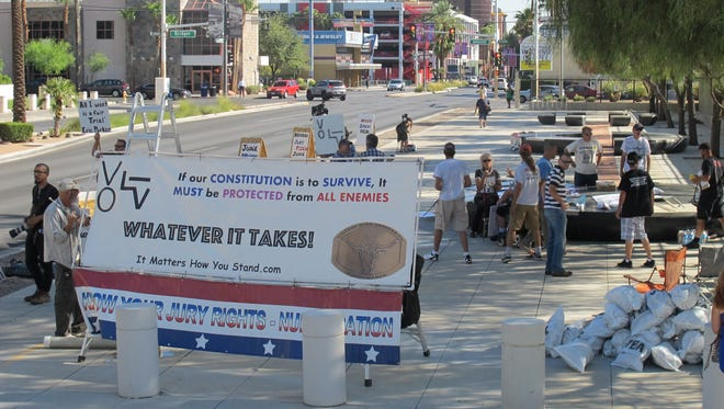 "Supporters of defendants in the Bundy Ranch standoff trial stand outside U.S. District Court in Las Vegas on Aug. 14, 2017. The supporters piled up ""tea bags"" as a reminder of liberty."