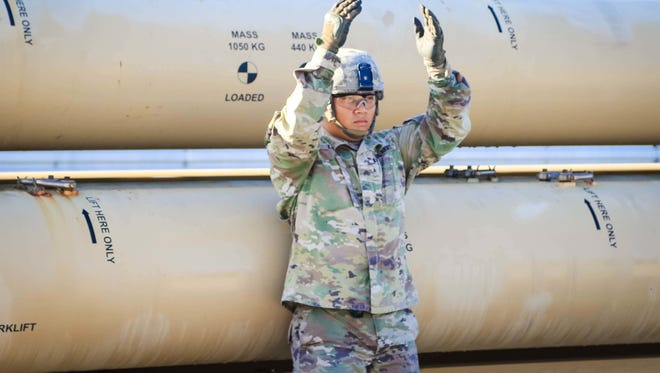 Sgt. Wifredo Lopez with Task Force Talon, 94th Army Air and Missile Defense Command, guides a military forklift forward to lift a missile round trainer on Andersen Air Force Base, Guam, Oct. 26, 2017.