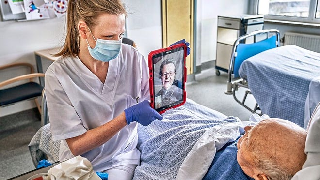 A nurse helps a nursing home resident have a virtual visit with a family member during the COVID-19 pandemic.