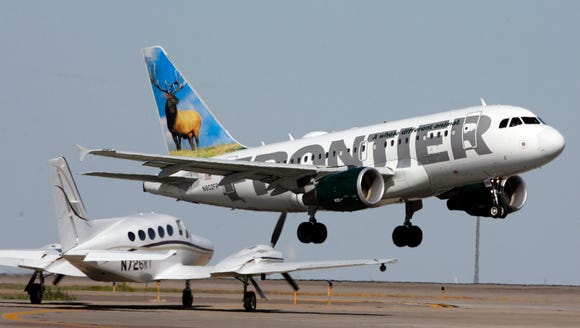 A Frontier Airlines airplane takes off from   Denver