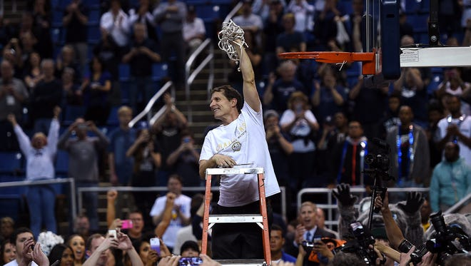 Nevada head coach Eric Musselman cuts down the net after defeating Morehead State in overtime to win the College Basketball Invitational tournament championship at Lawlor Events Center in Reno on April 1, 2016.