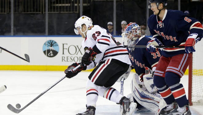Chicago Blackhawks right wing Kris Versteeg (23) corrals the puck in front of Rangers defenseman Anton Stralman (6) and goalie Cam Talbot (33) during the first period at Madison Square Garden on Feb. 27, 2014.