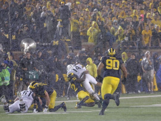 MSU's Brian Lewerke is tackled by U-M's David Long in a rain-soaked win for the Spartans at Michigan Stadium on Oct. 7, 2017.