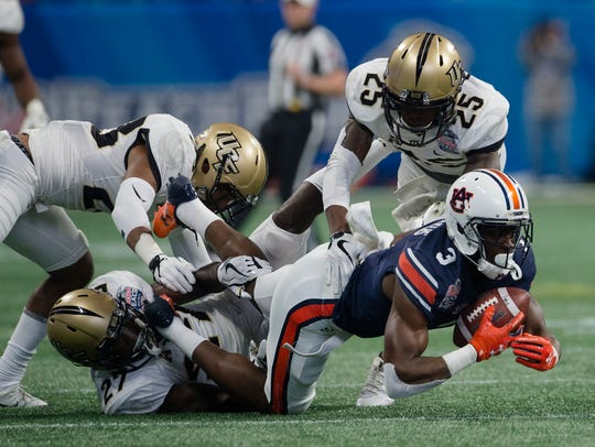 UCF defensive back Richie Grant (27) tackles Auburn