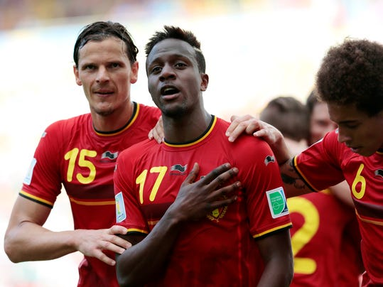 """FILE - In this Sunday, June 22, 2014 file photo, Belgium's Divock Origi, center, celebrates with teammates Daniel Van Buyten, left, and Belgium's Axel Witsel, right, after Origi scored the opening goal during the group H World Cup soccer match between Belgium and Russia at the Maracana stadium in Rio de Janeiro, Brazil. Liverpool says it has signed Belgium striker Divock Origi from Lille and will loan him back to the French club for the whole of next season. The 19-year-old forward, who impressed during Belgium's run to the quarterfinals of the World Cup, completed his transfer in the United States - where Liverpool is on a pre-season tour. The club said he had signed a """"long-term deal"""" without giving details. British media put the transfer fee at 10 million pounds ($17 million). Origi, who joined Lille from Genk in 2010, says """"Liverpool is one of the greatest clubs in the world and I'm very excited to be part of this great history."""" (AP Photo/Ivan Sekretarev, file)"""