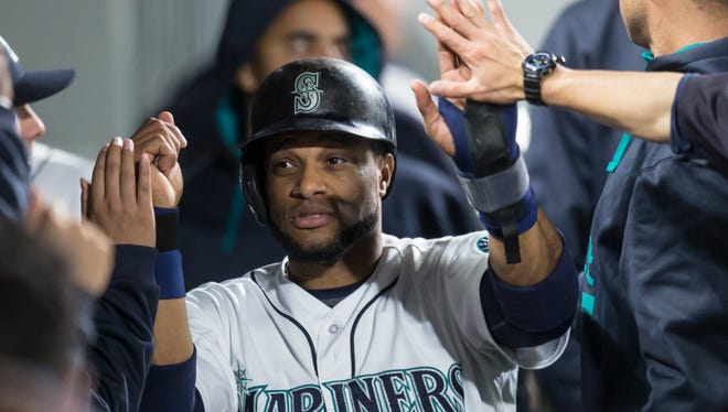Seattle Mariners' Robinson Cano is congratulated after scoring a run on wild pitch by Houston Astros' Scott Kazmir during the second inning of a baseball game Wednesday, Sept. 30, 2015, in Seattle.