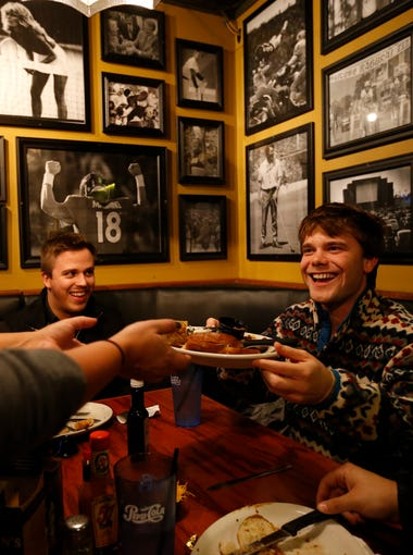 C.G. Niquette (right) hands his plate off to his server as he has a late dinner with fellow campaign staff member Casey Clemmons (left) Monday, Dec. 14, 2015, at Wellman's Pub on Ingeroll in Des Moines. Both Niquette and Clemmons work for Democratic presidential candidate Hillary Clinton's campaign in Iowa.